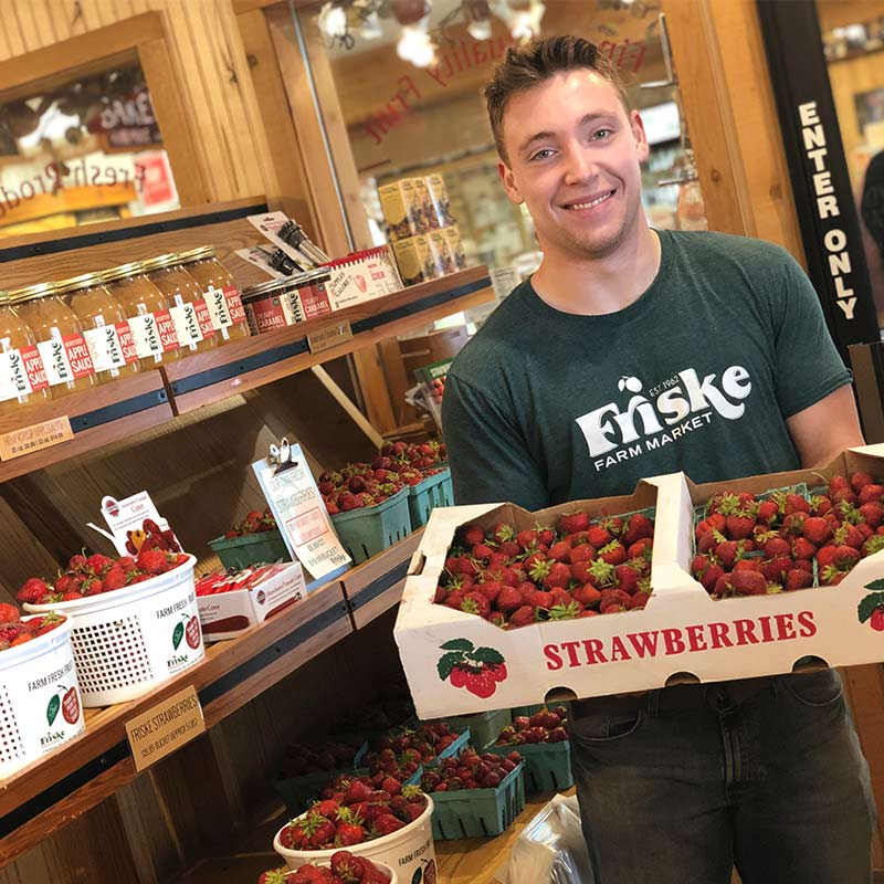 friendly-staff-with-strawberries-at-fruit-stand